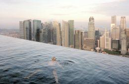 Un uomo galleggia nella piscina al cinquantasettesimo piano del Marina Bay Sands Hotel. Alle sue spalle lo skyline di Central, il distretto finanziario di Singapore. © Gabriele Galimberti & Paolo Woods