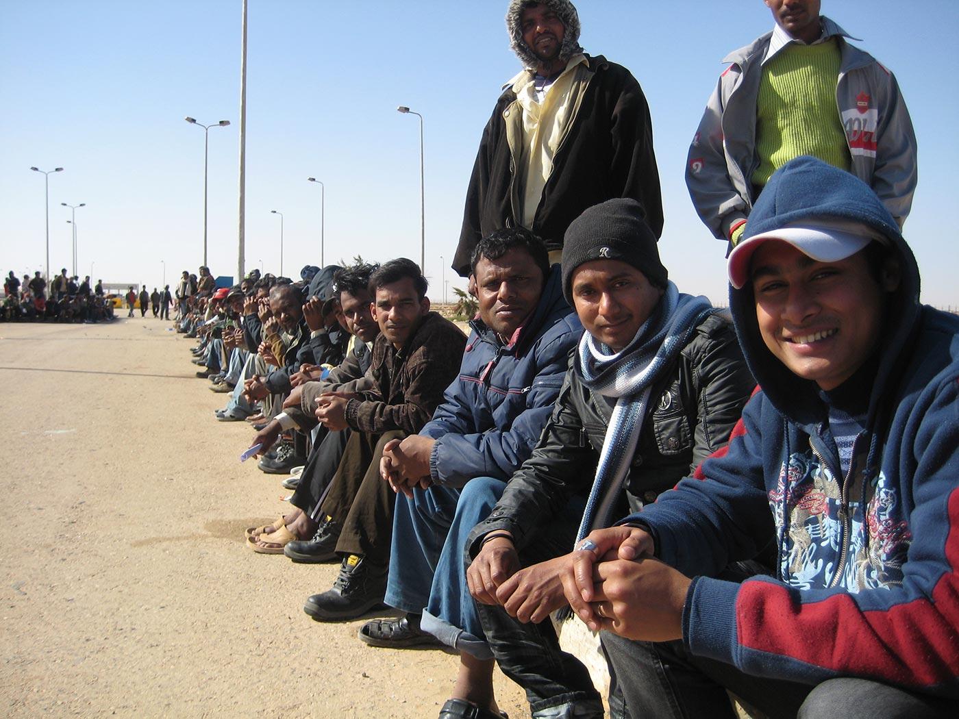 Lavoratori bengalesi sorridono tesi alla fotocamera, mentre attendono di essere rimpatriati. Foto CC UK DFID