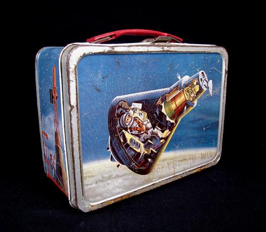 Thermos, 1963. Schiscetta rara, perché Thermos non aveva pagato a National Geographic la licenza per l'uso dell'immagine del modulo Mercury, per cui la lunch box è stata ritirata molto presto dal commercio.