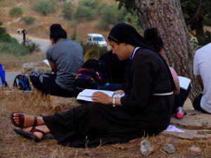 Una suora intenta a pregare distesa su di un prato, Galilea