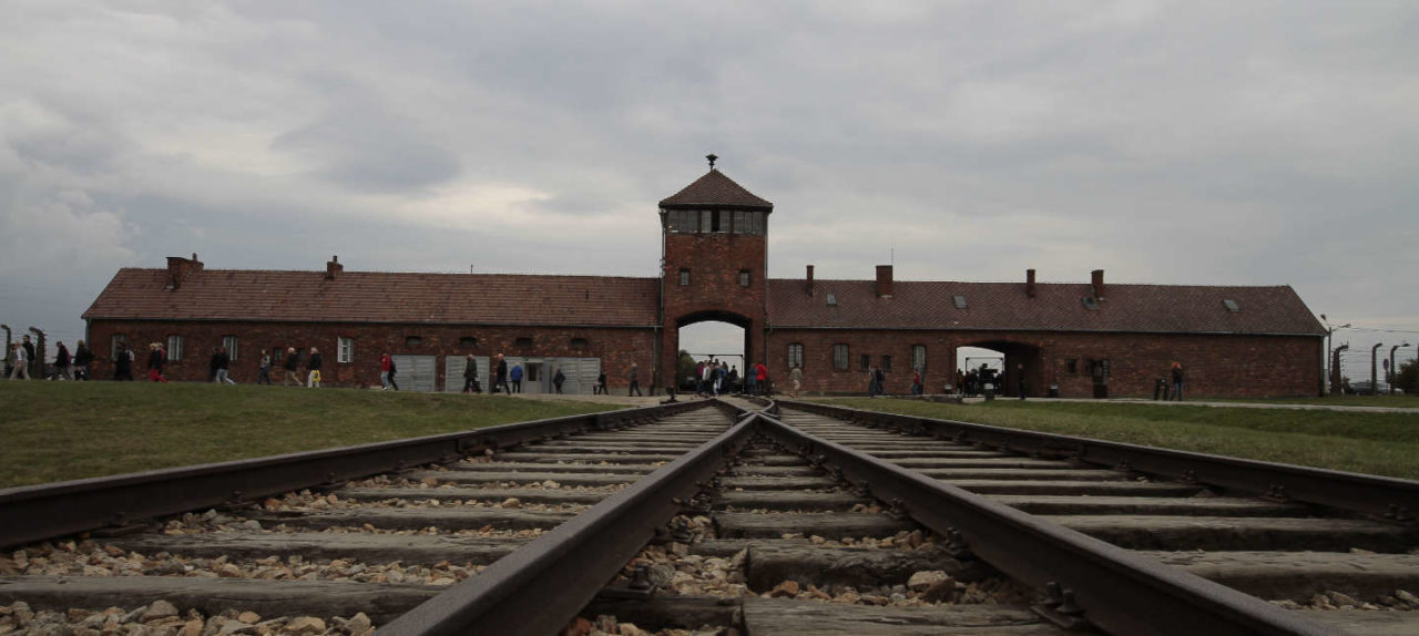 https://thesubmarine.it/wp-content/uploads/2018/02/Main_entrance_to_the_Auschwitz_II-Birkenau-1280x574.jpg