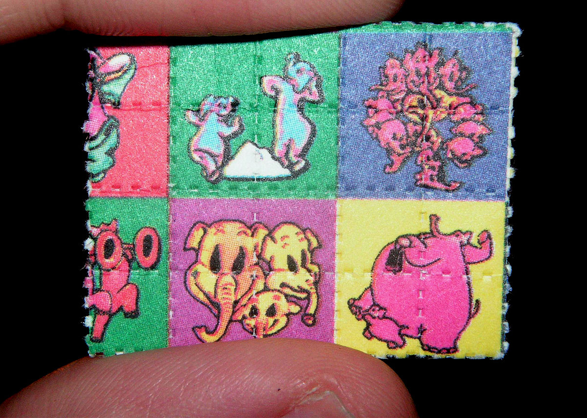 https://thesubmarine.it/wp-content/uploads/2018/05/1200px-Pink_Elephants_on_Parade_Blotter_LSD_Dumbo.jpg